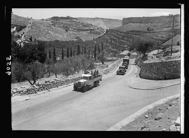 Palestine disturbances 1936. Long line of Jewish buses returning from funeral under police escort