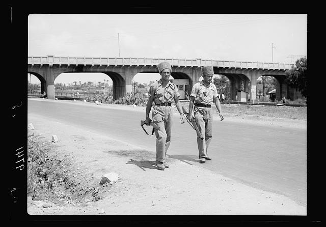 Haifa, result of terrorist acts & government measures. H.M.S. 2 Jewish Supernumerary Police patrolling Nazareth road outside Haifa close to Jewish settlements. Haifa Shell Bridge in background