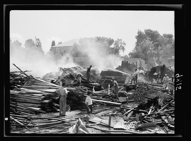 Same fire [night incendiary of coal and lumber yards near railroad station] still burning on following morning