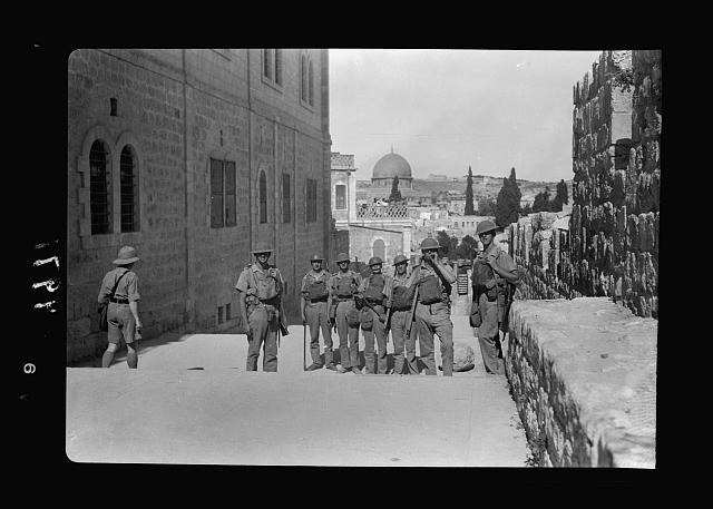 The raising of the siege of Jerusalem. Typical scene of troops in Cld City before the lifting of curfew, troops along south city wall, Dome of the Rock in distance