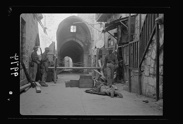 The raising of the siege of Jerusalem. Typical scene of troops in Old City before the lifting of curfew. War-like scene in Bab el-Silseleh quarter with machine-gun in foreground, entrance to Mosque grounds in distance
