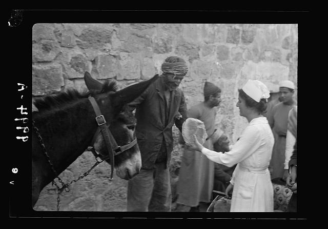 The raising of the siege of Jerusalem. Nurse handing over loaf of bread to an old town scavenger