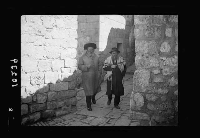 Orthodox Jews on their usual Sabbath walk to the Wailing Wall (2 men, one with prayer cl[oth])