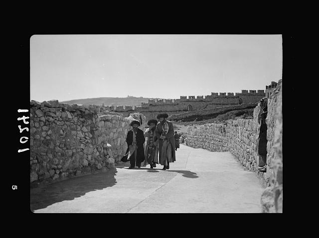 Orthodox Jews on their usual Sabbath walk to the Wailing Wall (3 men, city wall in backg[round])