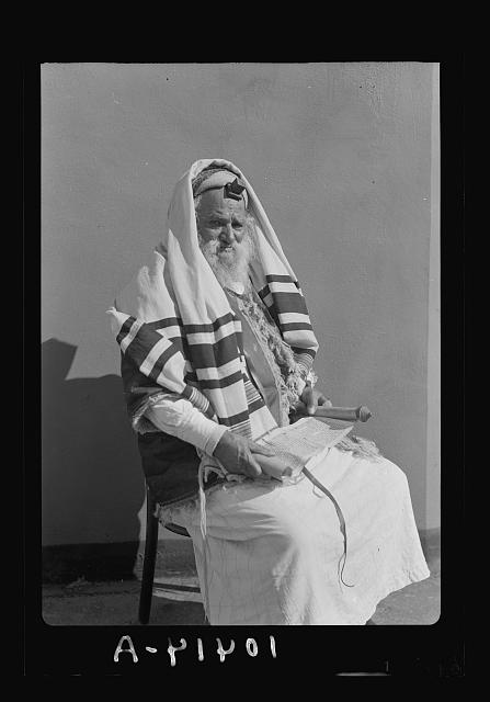 Abram [Yemenite Jew] with book in hand, reading scroll (Magella) with phylacteries on forehead