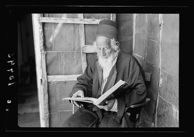 Rabbi Shlomo, reading the Torah, seated in his home
