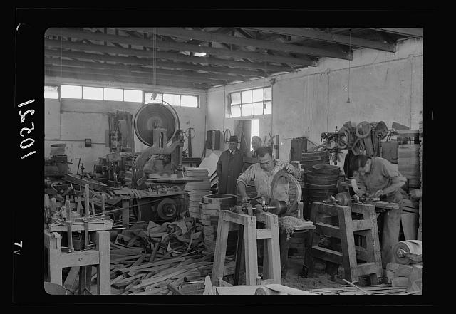 Jewish factories in Palestine on Plain of Sharon &amp; along the coast to Haifa. Bent Furniture Factory in Holon Settlement. Dressing chair bottoms by machinery, closer up