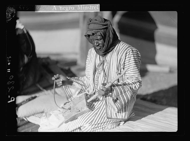 Trans-Jordan types. Bedouin music. A Negro minstrel. (Performing for guests)