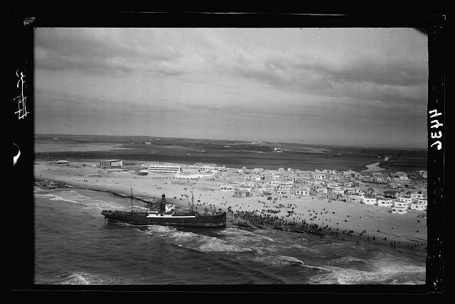 Air views of Palestine. Jaffa, Auji River and Levant Fair. Grounded orange steamer on Tel Aviv coast. Crowds of spectators on a Sabbath day