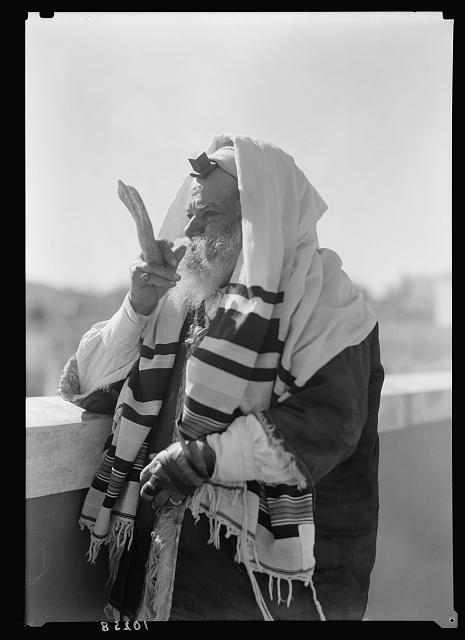 Yemenite Rabbi Avram arrayed for prayer, blowing the shofar