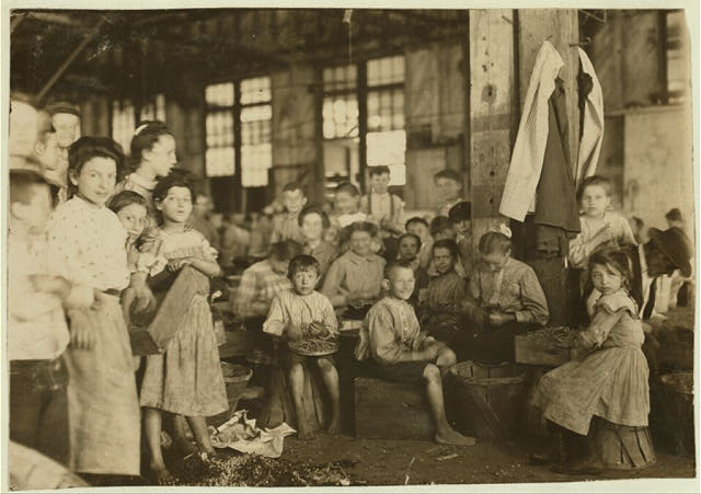 Groups showing a few of the workers stringing beans in the J. S. Farrand Packing Co., Baltimore, Md. Those too small to work are held on laps of workers or stowed away in boxes.  Location: Baltimore, Maryland.