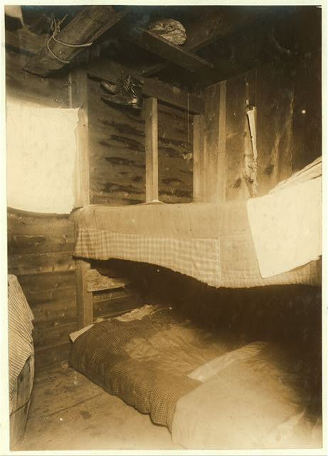 Room 21 in Shanty # 2, in settlement called Rome, on White's Bog, Browns Mills, N.J. 3 persons live here, cranberry pickers. Family of Rocco De Gruerio. Room is 6 ft. x 7 ft. and 7 ft. high. Window is 22 x 18 inches. One bed on floor. Note the bread and shoes hanging over the bed. Plenty of flies. E.F. Brown [Witness].  Location: Browns Mills, New Jersey.