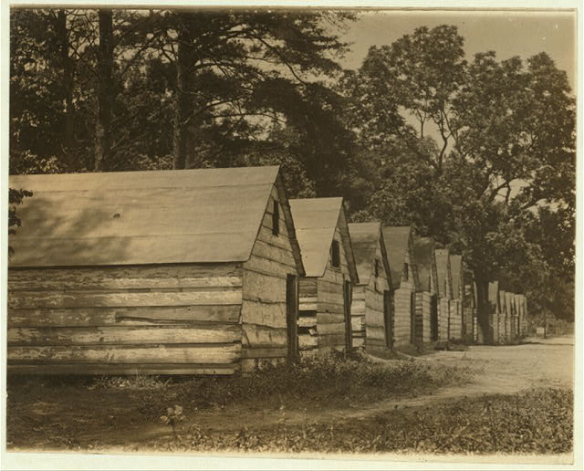 The negro berry pickers shacks on the farm of Col. J. J. Ross, Del. The interior of these shacks consists of a flooring of straw, a few bags, and absence of light and air.  Location: Ross, Delaware.