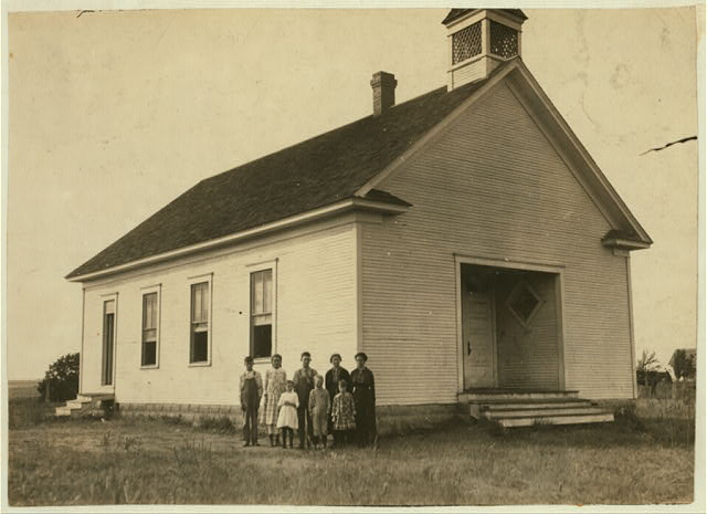 Pioneer School #13 (6 miles northwest of Shawnee) opened October 2nd--7 months term. Miss Lela Ginsinger, Principal (been here 2 years). Photo shows only 6 children present and 2 teachers in the third week of school. Expect 24 pupils. All absences are due to cotton. A few of the larger ones will be out in the Spring for cotton. Lewis W. Hine. See W.H. Swift Report.  Location: Potawotamie County, Oklahoma.