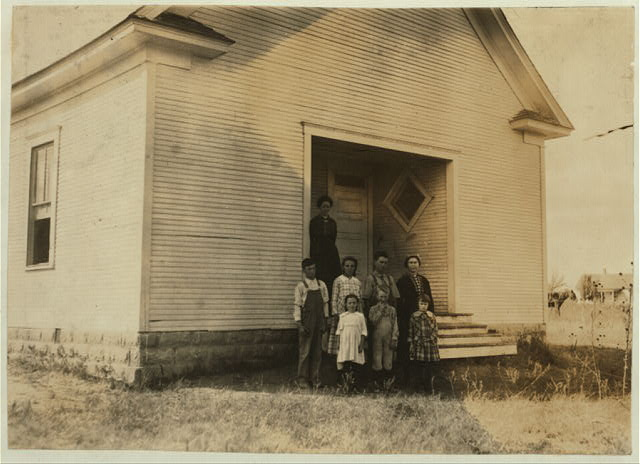 [Pioneer School #13 (6 miles northwest of Shawnee) opened October 2nd 7 months term. Miss Lela Ginsinger, Principal (been here 2 years). Photo shows only 6 children present and 2 teachers in the third week of school. Expect 24 pupils. All absences are due to cotton. A few of the larger ones will be out in the Spring for cotton. Lewis W. Hine. See W. H. Swift Report.]  Location: [Potawotamie County, Oklahoma]