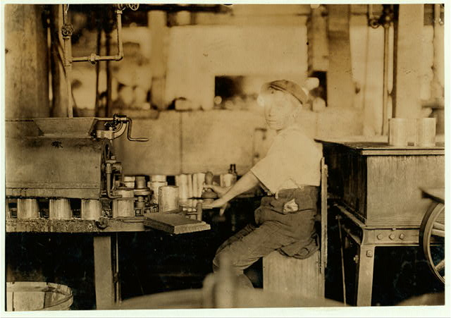 Name: Dangerous Business. Boy working at canning machine with open gearing. Many suck machines and boys too. J. S. Farrand Packing Co. Witness--J. W. Magruder. July 7, 1909.  Location: Baltimore, Maryland.