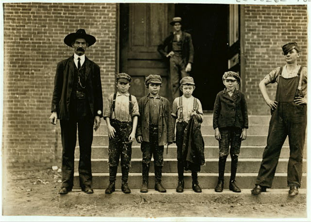 "Boy with coat in hand is 11 years old. Been there 9 months. Started at 50 cents a day. Now gets 60 cents. Loray Mill. ""When I sweeps double space I gets 90 cents a day, but it makes you work. "" (Look at the boy.) Two ""infants"" appeared at the door, and vanished back immediately on seeing me.  Location: Gastonia, North Carolina."