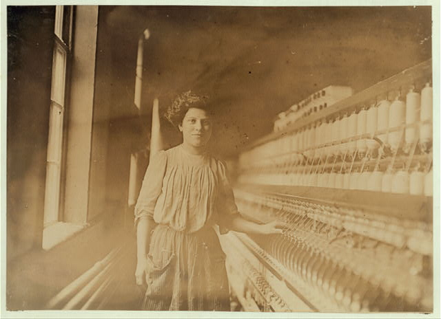 [A beautiful young spinner and doffer in Interlaken Mill, Arkwirght, R. I. She has worked there 1 year. Looked 12 yrs. old and had a hectic flush caused by warm, close atmosphere.]  Location: Arkwright, Rhode Island.