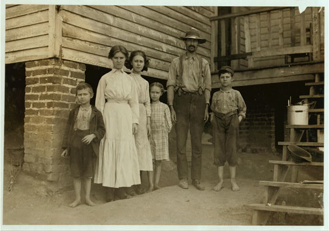 T.J. Fields and family. The father cards, two girls spin, boy on right end picks up bobbins, Washington Cotton Mills, Fries, Va. Been working a year or two. Mother and smallest children not in photo.  Location: Fries, Virginia.