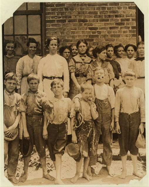 "Group showing most of the youngsters working in the Cowpen's Manufacturing Co., S.C. They are all regular workers including shorty the smallest one. The boy next to him was dragged out of the photograph against his will soon after by an anxious parent. Superintendent was very suspicious and accused me of being the one who made so much trouble for the mill people several years ago. He finally permitted some outside photographs only saying, ""We have certificates for all these children.""  Location: [Cowpens], South Carolina."