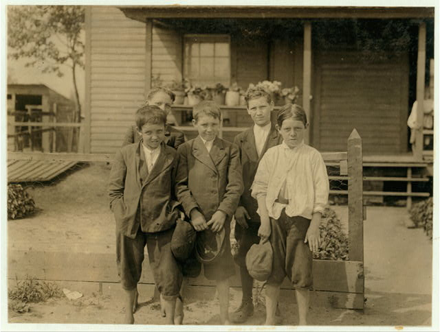 Group of mill boys going to church Sunday morning. Beaumont Mill Settlement, Spartanberg, S.C. All work. The front row left hand and Elish Putnam been working 3 or 4 years. Middle Bryson Hemmett working 3 months. Right hand George Powell, six months working.  Location: Spartanburg, South Carolina.