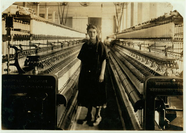 [Girl standing between looms.]  Location: Fall River, Massachusetts