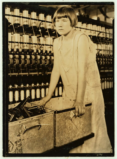 Cheney Silk Mills. Favorable working conditions. [Young girl worker at Cheney Silk Mills, leaning on scrap metal wagon, S. Manchester, Conn.] (No. 5002).  Location: [South Manchester, Connecticut]