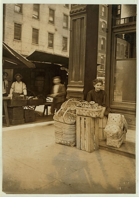 Lena Lochiavo, 11 years old, 209 W. Sixth St., Basket Seller, Sixth Street Market, Cincinnati. In front of saloon entrance.  Location: Cincinnati, Ohio.