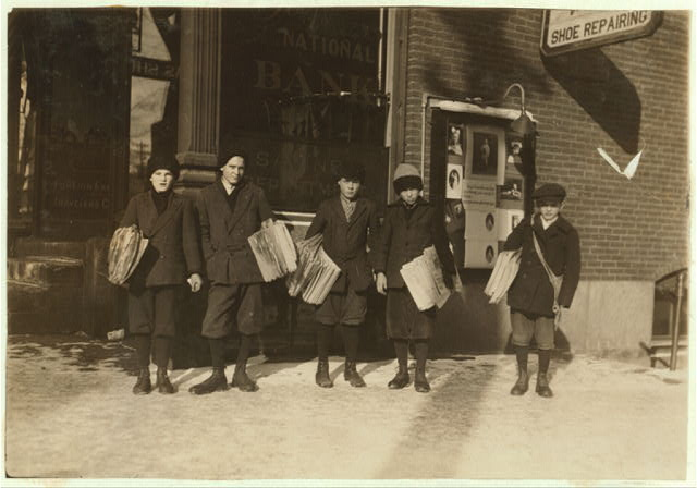 Group of newsies (youngest 10 years) selling Boston papers at noon. In Barre and Montpelier newsies are excused from school a little early at noon and at night in order to get to their papers earlier.  Location: Barre, Vermont