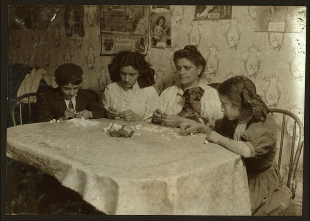 Gizzi family, 175 Sullivan St., 3:30 P.M. Make little roses which are easier than violets, but bring only 9 cents gross. Left to right: Leo, 11 years old. Louise 14 years old. Jose 12 years old. Work after school and Saturday.  Location: New York, New York (State)