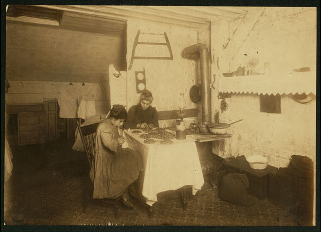 Tessie Sposato, 12 yrs. old girl and her mother picking nuts in attic of tenement, 141 Hudson St., N.Y. She holds the nuts against her dirty apron as she picks them out. Works until 9 p.m. some nights. They live in 2 small rooms; paying $5.00 a month rent. Makes $2.00 a week. A 15 yr. old brother works in factory and sleeps in folding bed in this room.  Location: New York, New York (State)