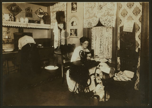 Annie Maier (or Meyer), making Campbell-Kids' pinafores in her basement home, 71 [?] E. 108th St. She was reported to have tuberculosis. Working in the Kitchen. (See also #2715).  Location: New York, New York (State)