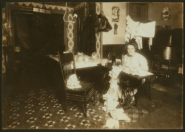 Annie Maier (or Meyer), making Campbell-kids' pinafores in her basement home. 71 E. 108 Street. She was reported to have tuberculosis. Working in the kitchen. (see also No. 2713).  Location: New York, New York (State)