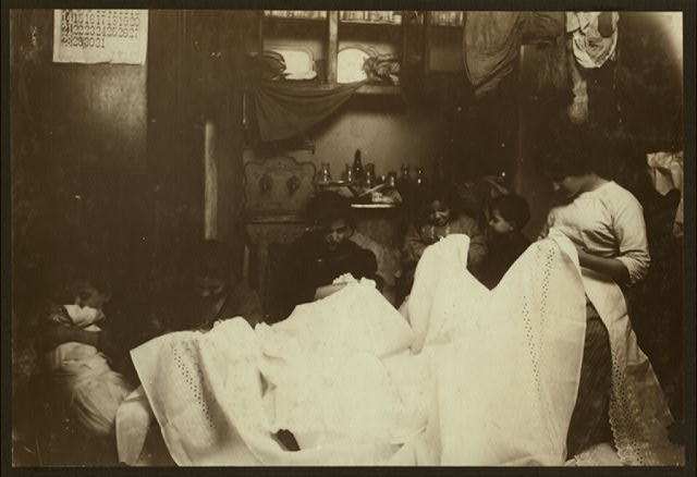 """Cutting out embroidery on the dirty kitchen floor. Battista family, 259 E. 151 St. N.Y. On the right is the married daughter, who lives down stairs and usually works there. On her right next to the boy is Flora, said to be 9 years old and very much stunted in size. """"Been sick."""" Next to her is the mother and next is Linda, 11 years old. The baby, dirty and covered with sores, was being handed about. Probably has impetego.  Location: New York, New York (State)"""