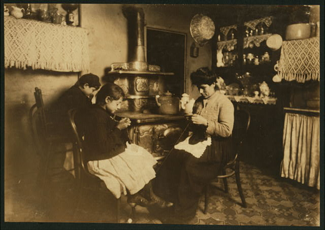 "Antoinette Fazzino, ten years old, makes Irish lace for collars and waists, after school. Her younger brother (by the stove) said, ""Lace is too dam-cheap."" Antoinette wears glasses. 303 E. 149th Street, N.Y.  Location: New York, New York (State)"