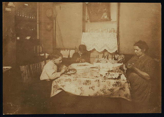 A Night Scene (Photo by 9:00 P.M.) Flower making. Family of Mary Bezzola, 212 Sullivan St., N.Y. George (10 years old) and Levia (9 years old) work until 9:00 P.M. when work is rushing.  Location: New York, New York (State)