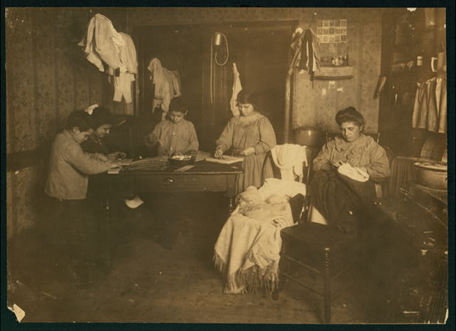 6 P.M. Callabria family, 647 E. 12th St., N.Y. (see schedule) Mother finishes clothing. The children paste needle packages onto cards and said they all work at times until 10 or 11 P.M. They are 9, 12, 14 and 15 years old and all go to school. They are undersized. The baby in the cart is one month old.  Location: New York, New York (State)