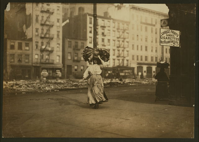 Woman carrying heavy bundle of clothing to be finished at home. Near Astor Place, N.Y.  Location: New York, New York (State)