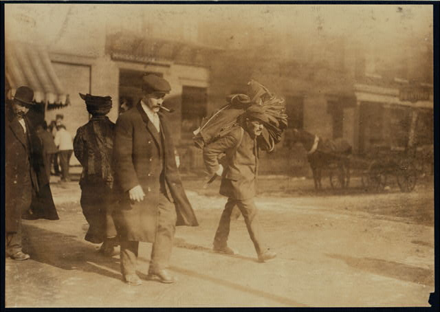 Man straining to carry heavy bundle of clothing. They carry these for long distances, often. East Side, N.Y.  Location: New York, New York (State)