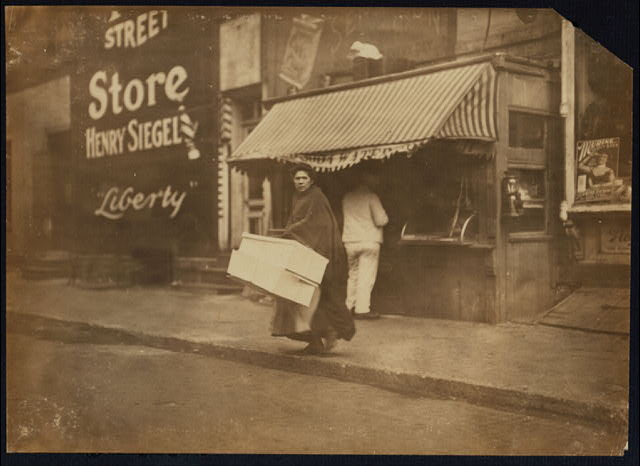 A mother carrying flowers home to be made. 210 Sullivan St., N.Y. (see 2851).  Location: New York, New York (State)