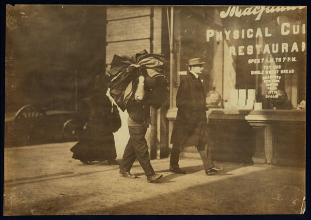 Man carrying bundle of garments. Bleeker St., N.Y.  Location: New York, New York (State)