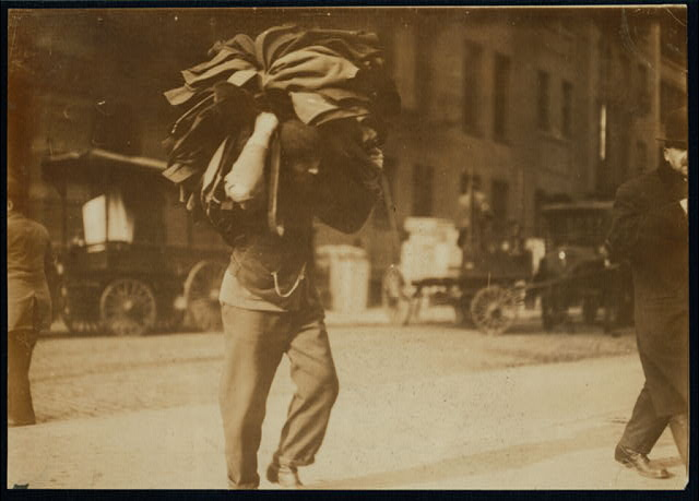 Man carrying bundle of garments. Bleeker Street, N.Y.  Location: New York, New York (State)