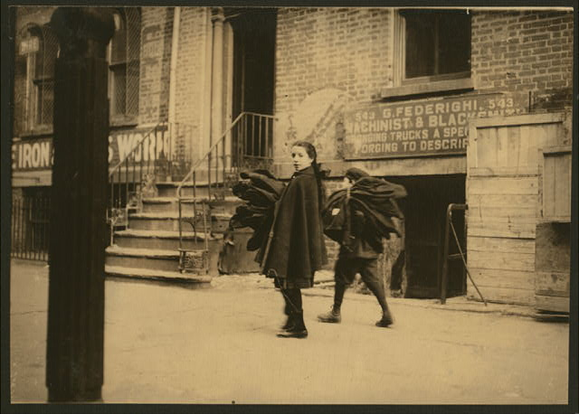 Nine and twelve-year-old children carrying coats home to be finished. Thompson St., N.Y.  Location: New York, New York (State)