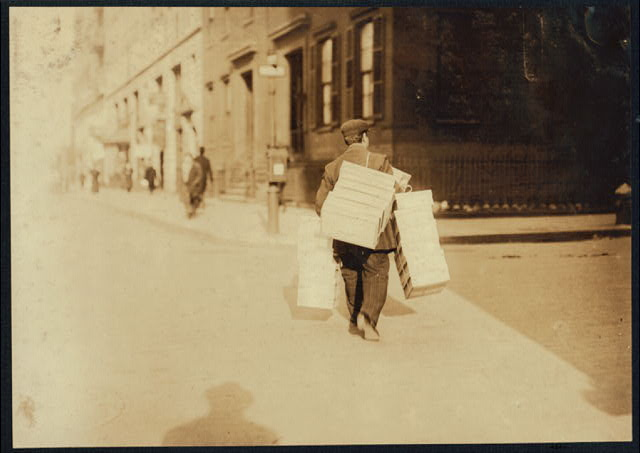 Man carrying load of caps made at home to factory, 9-11 University Place, --- Feldstein's.  Location: New York, New York (State)