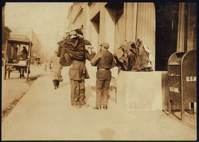 A moment's rest. These bundles are often carried long distances. When the man gets tired, he drops the clothing onto a convenient box or railing, disregarding dust or dirt. Makes button holes at home. Washington Square, N.Y.  Location: New York, New York (State)