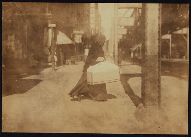 Woman carrying flowers home. W. Broadway, N.Y.  Location: New York, New York (State)