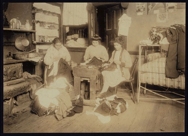 "Pallagi (?) family finishing pants, 17 Monroe St., N.Y., 2nd floor front. None of them spoke any English. A neighbor's child said the young girl is 13 yrs. old. Photo taken at 2:45 P.M. Mar./6/12, a school day. In the next apartment, a 12 yr. old girl was finishing pants and explained, ""I came home with the toothache.""  New York, New York (State)"