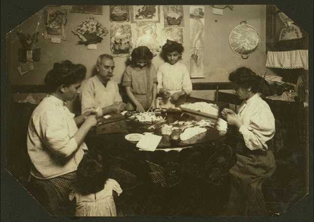 Whole family rolling cigarette cases, the mother was licking the papers as she worked. (For complete details see Miss E.C. Watson's report.)  Location: New York, New York (State)