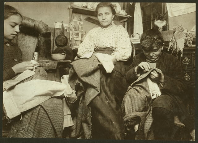 High up on the top floor of a rickety tenement, 214 Elizabeth St., N.Y., this mother and her two children, boy 10 years old and the girl 12, were living in a tiny one room, and were finishing garments. The garments were packed under the bed and on top of it and around the room. Said the make from $1 to $2 a week, and the boys [sic] earns some selling newspapers. I could not get their name.  Location: [New York, New York (State)].
