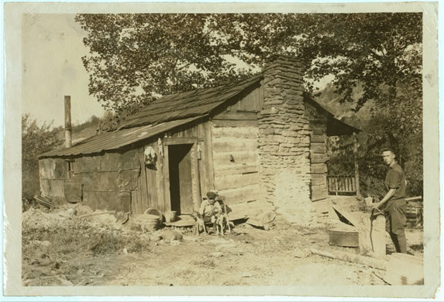 A little log cabin, - relic of the old days, - now occupied by a small family (F.T. Castle) who are gradually giving up farming and depending upon mining and odd jobs. Oct. 12, 1921. (Dogs).  Location: Big Chimney, West Virginia